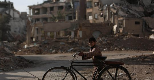 A child pushes his bike across the city, Eastern Ghouta.